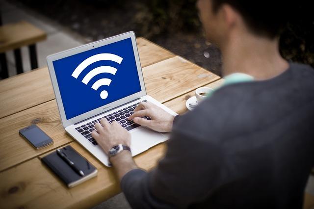 podnikatel, který sedí u počítače a přes WiFi připojení může sledovat vozový park
