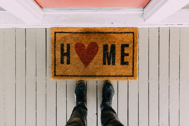Pohled na boty a rohožku home přede dveřmi na bílých prknech